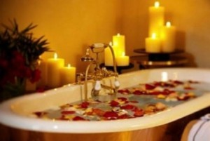 Photo of a bath with candles and rose petals