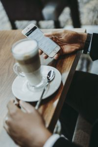Man at a cafe table with his phone and a coffee