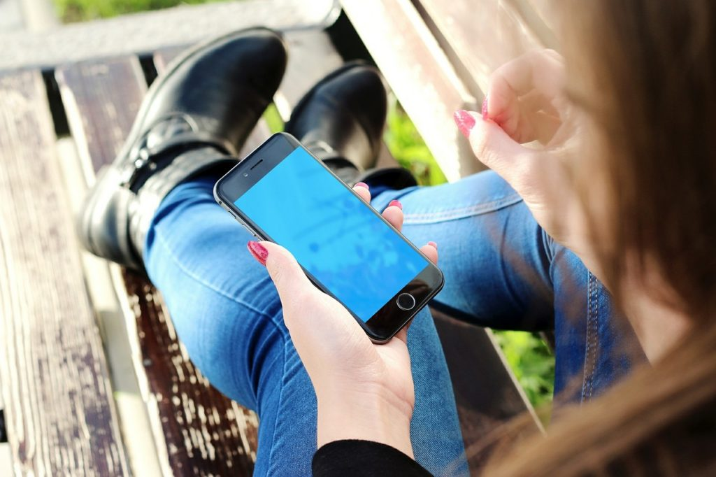 Woman sitting on a bench using her phone