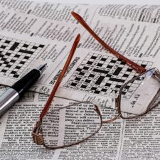 Crossword puzzle with glasses and pen lying on top