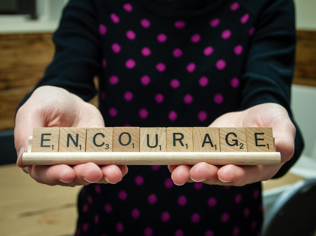 Scrabble tiles on a rack spelling out 'encourage'