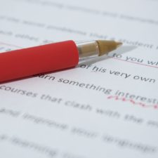 Red pen resting on annotated essay