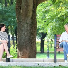 Two women sitting on different park benches, looking at each other