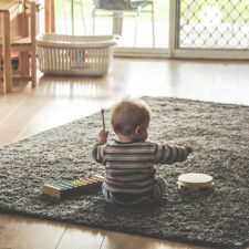 Toddler on a mat with a xylophone and tambourine