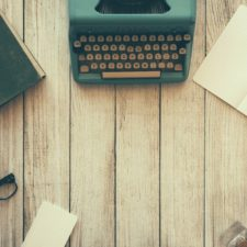 Typewriter on a desk with notepad and writing implements